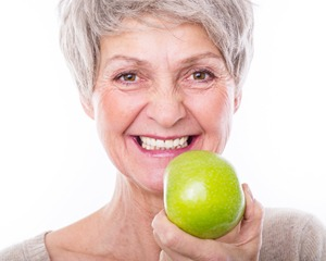 Smiling older woman holding green apple