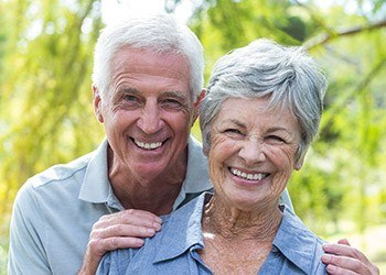 Senior man and woman smiling outdoors