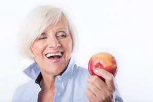 Woman with white hair wearing a light blue shirt is looking at an apple and smiling